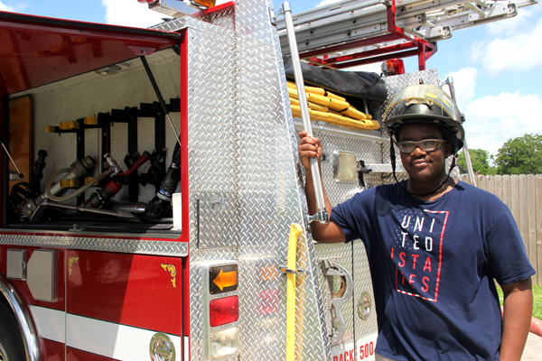 Pictured, student Jo-'el Pickett-Frederickson explores COM's fire engine and firefighter equipment.